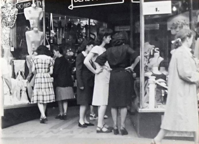 Women standing in front of a $ 1 Sign in a Shopwindow
