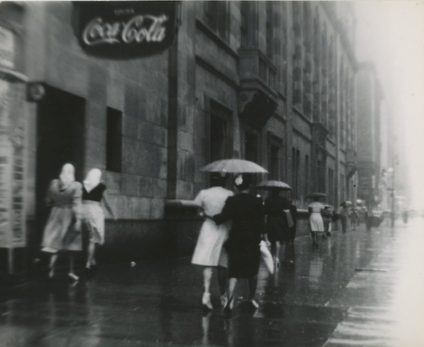 Women in the Rain under a Coca Cola Sign