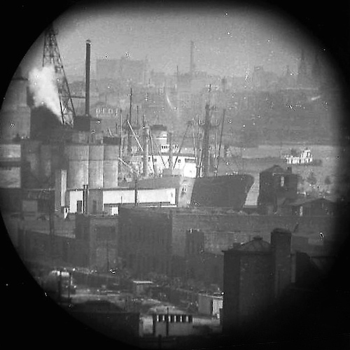 Cargo steamers, docked, East River (telescope view)