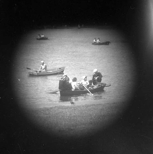 Central Park rowing boat with two Navy sailors and pigeon (telescope view)